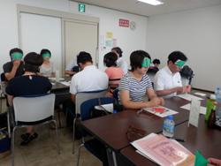 先生方がアイマスクをつけ折り紙をしているところ