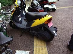 誘導ブロックの上にバイクや自転車が止めてある写真