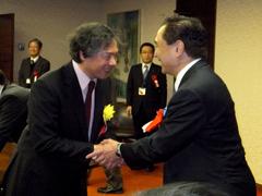 授賞式で黒岩県知事と両手で硬く握手をする新城理事長の写真