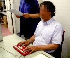 パソコンとつながったキーボード(6点入力用)を使っている男性、 墨字の資料を持っている女性が横にいる写真